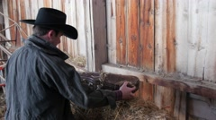 Cowboy finds a fiddle in his old barn Stock Footage