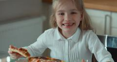 Child eating pizza. Smiling at camera and laughing Stock Footage