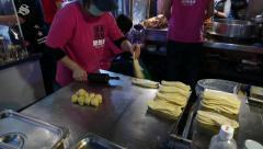 Woman roll and flatten dough ball, to make pancake shape. Repeating process Stock Footage