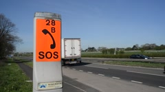 sos emergency telephone on dual carriageway road united kingdom - stock footage