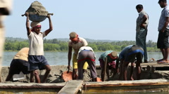 Men taking sand out of a boat in Goa. Stock Footage