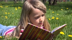 4K Child Little Girl Reading a Storybook in Park, Kid Playing Book Meadow Grass - stock footage