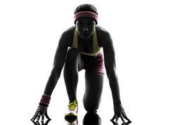 Woman runner running on starting blocks silhouette Stock Photos