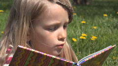 Portrait Face Child Girl Reading Storybook in Park Kid Playing Book Meadow Grass - stock footage