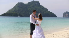groom lifts bride in arms and she kisses him on  beach against island and sea - stock footage