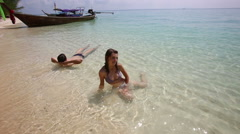 girl and guy swim in transparent azure sea near boat - stock footage