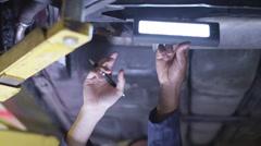 4K Team of mechanics working underneath a car in garage workshop Stock Footage