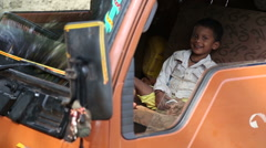 Indian boy sitting on the front seat of a truck. Stock Footage