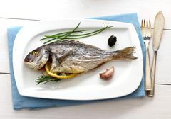 Garnished grilled whole sea bream with olives Stock Photos