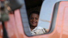 Portrait of Indian boy sitting on the front seat of a truck. - stock footage