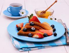 Pancakes and honey dipper on blue wooden - stock photo