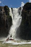 Dinghy under the  the Iguazu Falls - stock photo