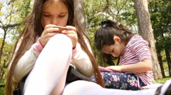 Two girls playing games on tablet computer and phone sitting in park Stock Footage