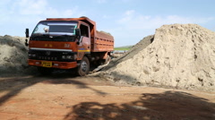 Men transporting bowls full of sand to a pile of sand by the truck. Stock Footage