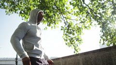 4K Athletic black male taking a break from running to stretch out in urban envir Stock Footage