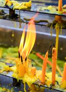 Close up yellow candles with flame in temple - stock photo