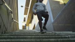 4K Athletic black male running through urban environment Stock Footage
