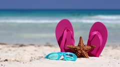 Pink flip flops, swimming glasses and starfish on white sandy beach Stock Footage