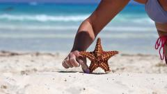 Putting starfish in sand on caribbean sandy beach, travel concept Stock Footage