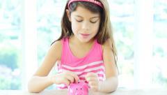 Tilt-down shot of little girl and piggy bank Stock Footage