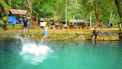VANG VIENG, LAOS - CIRCA DEC 2013: Tourists splashing into the cool, refreshi Stock Footage