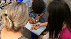A woman using henna paste tattooing in Bangkok downtown Stock Footage
