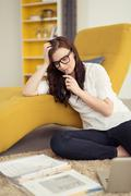 Thoughtful Young Woman Staring at her Workbook - stock photo