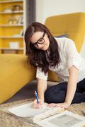 Happy Girl Answering her Workbook on the Floor - stock photo