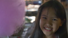 Little Asian girl eating cotton candy Stock Footage