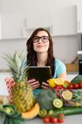 Girl Holding Tablet Behind Fruits and Veggies Stock Photos