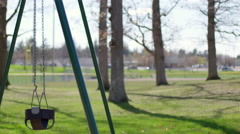 Side view of playground swings with boy swinging forward in and out 4K Stock Footage