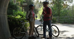 Mature couple talking on bike trail - stock footage