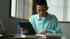 A young hispanic man studying with laptop and tablet Stock Footage