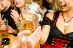 Bavarian girls drinking beer - stock photo