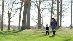 Mom and son walk towards viewer while holding hands 4K Stock Footage