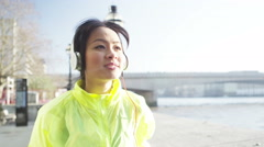 4K Athletic Asian woman running along a river with headphones, listening to musi Arkistovideo
