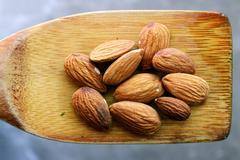 Stock Illustration of Almonds on wooden spoon