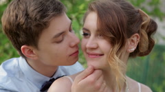 groom kisses the bride on a background of green leaves in spring - stock footage