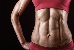 Close-up of the abdominal muscles young athlete on black background Stock Photos
