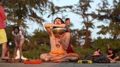 Man doing a religious ritual at sandy beach in Goa while people passing. Stock Footage