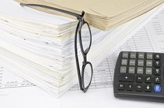 Stock Photo of Envelope on overload old paperwork with vertical spectacles and calculator