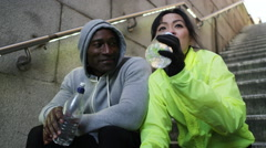 4K Athletic man and woman taking a break and drinking water in an urban environm - stock footage