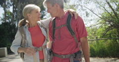 Senior couple walking and talking on trail Stock Footage