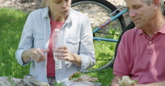Mature couple eating lunch after biking on trail Stock Footage