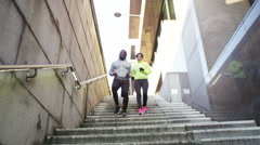 Stock Video Footage of 4K Athletic man and woman running together through urban environment