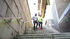 4K Athletic man and woman running together through urban environment Stock Footage