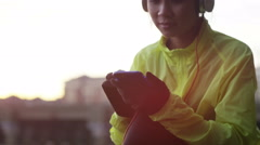 4K Athletic asian woman listening to music on her phone outdoors in the city Stock Footage