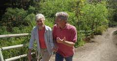 Happy mature couple walking on trail - stock footage