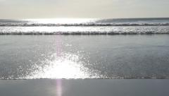 Slow motion ocean with smooth, flat, sunlit beach. Wave coming in. Stock Footage