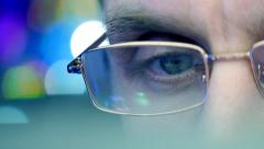 Reflection in the eye and glasses of the monitor when you surfing the Internet Stock Footage